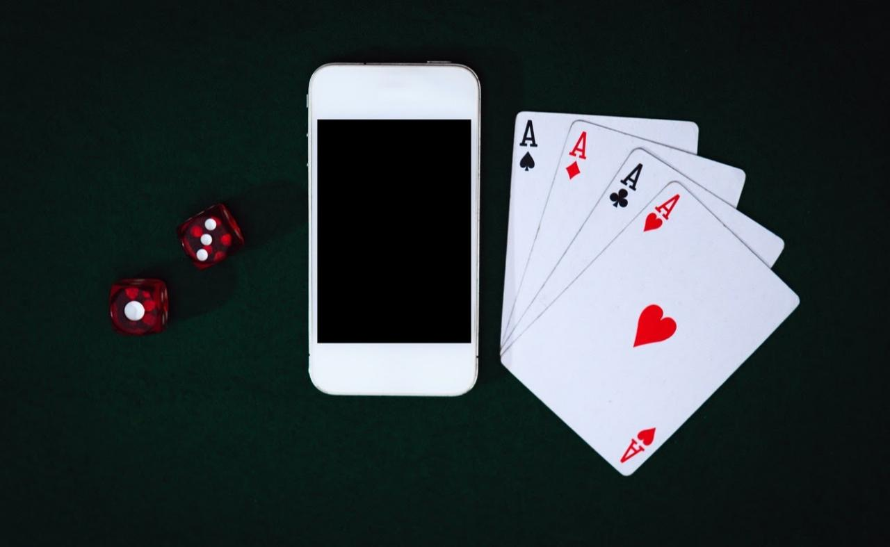 Close-up top view of smartphone, dices and cards on a green table